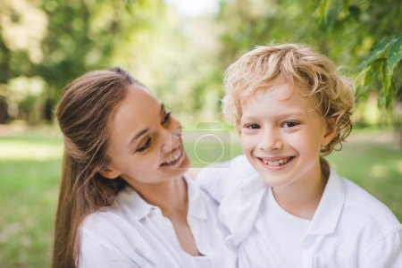 Photo for Beautiful mother with happy adorable son looking at camera in park - Royalty Free Image