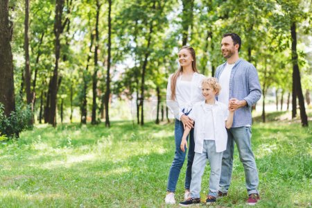 Photo for Happy family holding hands in park with copy space - Royalty Free Image
