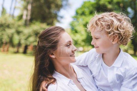 Foto de Hermosa madre feliz mirando a adorable hijo en el parque - Imagen libre de derechos
