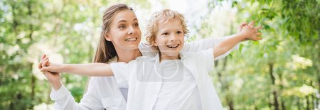 Photo for Panoramic shot of beautiful mother holding hands with adorable son in park - Royalty Free Image