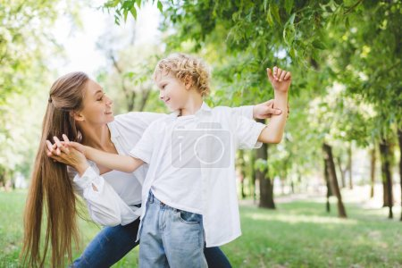 Photo for Beautiful happy mother holding hands with adorable son in park - Royalty Free Image