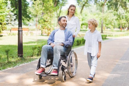 Photo for Mother and adorable son with disabled father on wheelchair in park - Royalty Free Image
