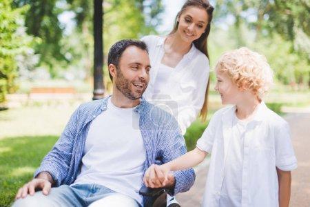 Photo pour Mère et fils adorable avec le père handicapé sur le fauteuil roulant dans le stationnement pendant la journée - image libre de droit