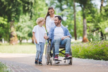 Photo for Beautiful mother rolling wheelchair with disabled father in park near son - Royalty Free Image