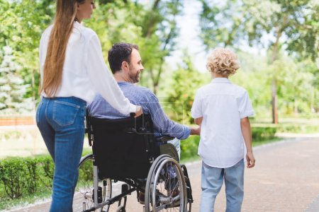 Photo for Back view of mother rolling wheelchair with disabled father in park - Royalty Free Image