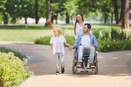 Photo pour Fauteuil roulant de mère avec le père handicapé dans le stationnement près du fils - image libre de droit