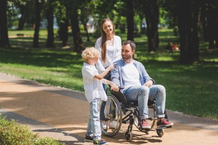 Photo for Beautiful mother and son with disabled father on wheelchair in park - Royalty Free Image
