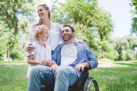 Photo pour Famille heureuse avec le père handicapé sur le fauteuil roulant dans le stationnement - image libre de droit