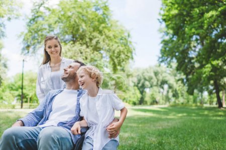 Photo for Happy mother and son with disabled father on wheelchair in park - Royalty Free Image