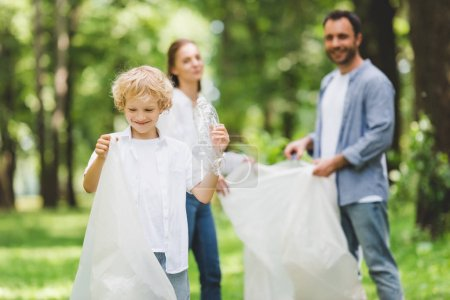 Photo for Happy family picking up garbage in plastic bags in park - Royalty Free Image