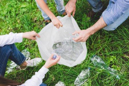 Photo pour Vue supérieure de la famille mettant des ordures dans le sac en plastique dans le stationnement - image libre de droit