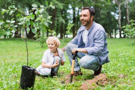 Photo pour Père et fils heureux avec le semis et la pelle dans le stationnement - image libre de droit