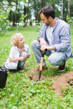 Photo pour Père et fils mignon pendant creuser le sol avec la pelle pour planter le plant dans le stationnement - image libre de droit