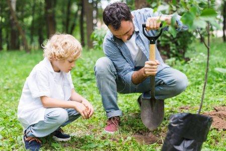Photo pour Père et fils pendant le creusement du sol avec la pelle pour planter le semis dans le stationnement - image libre de droit