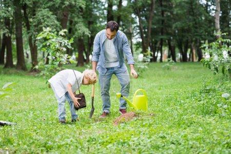 Photo pour Fils plantant le plantage dans le sol près du père dans le stationnement - image libre de droit