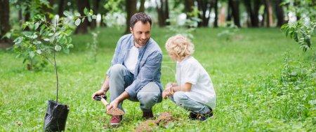 Photo pour Tir panoramique du père et du fils pendant le creusement du sol avec la pelle pour planter le semis dans le stationnement - image libre de droit