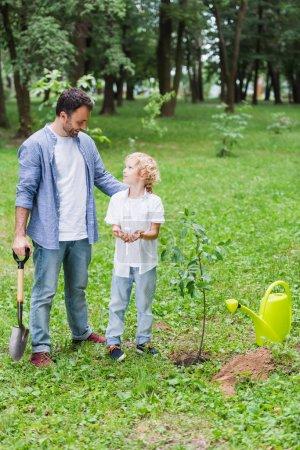 Photo pour Père avec le fils étreignant de pelle près de semis dans le stationnement - image libre de droit