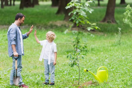 Photo for Father and son showing high five gesture during planting seedling in park - Royalty Free Image