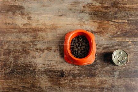 Foto de Vista superior del tazón y lata con alimentos para mascotas en la superficie de madera - Imagen libre de derechos