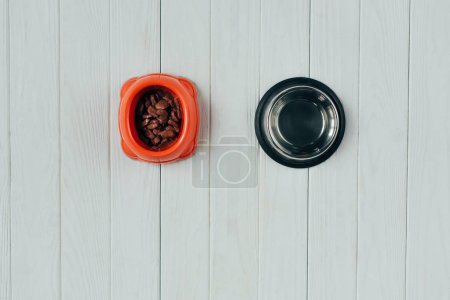 Photo for Top view of bowl with pet food and empty bowl on wooden surface with copy space - Royalty Free Image