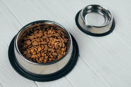 Photo for Metal bowl with pet food and empty bowl on white wooden surface - Royalty Free Image
