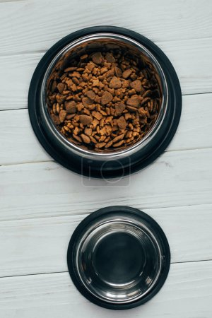 Photo for Top view of metal bowl with pet food and empty bowl on wooden surface - Royalty Free Image