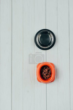 Photo for Top view of bowl with pet food and empty bowl on wooden surface - Royalty Free Image