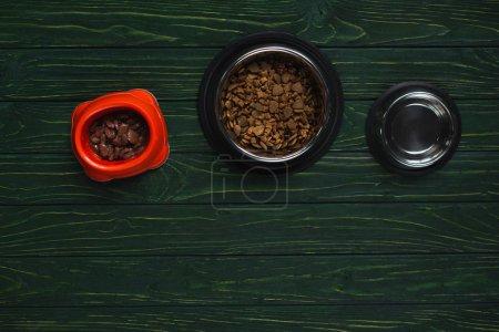 Foto de Top view of bowls with pet food in row on green wooden surface - Imagen libre de derechos