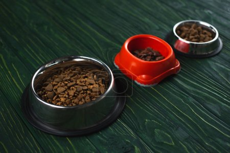 bowls with pet food in row on green wooden surface