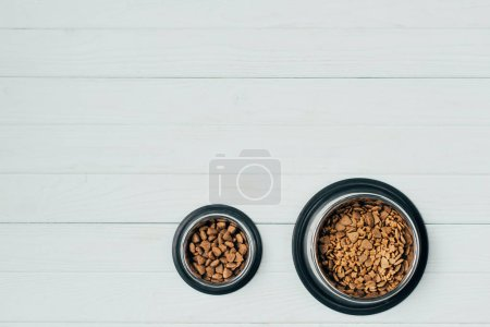 Photo for Top view of bowls with pet food on white wooden surface - Royalty Free Image