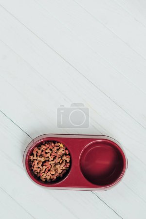 Photo for Top view of bowl with dog food on white wooden surface - Royalty Free Image