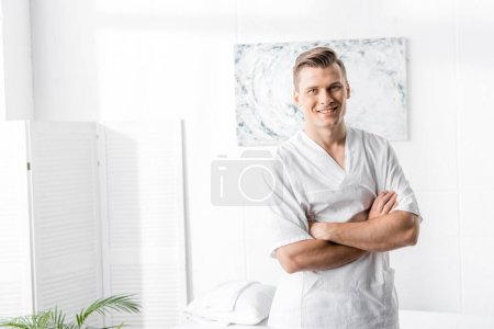 Photo for Smiling masseur standing with crossed arms and looking at camera in clinic - Royalty Free Image