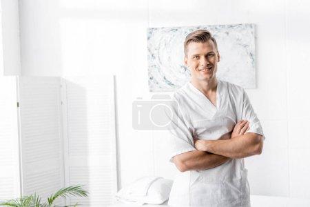 Photo pour Masseur souriant restant avec les bras croisés et regardant l'appareil-photo dans la clinique - image libre de droit