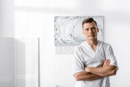 Photo for Masseur standing with crossed arms and looking at camera in clinic - Royalty Free Image