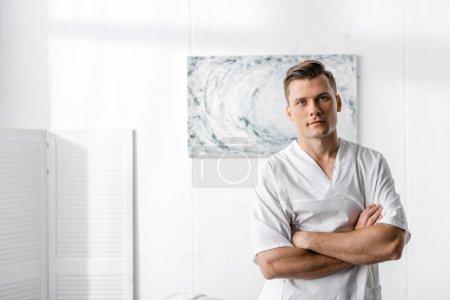 Photo pour Masseur restant avec les bras croisés et regardant la caméra dans la clinique - image libre de droit