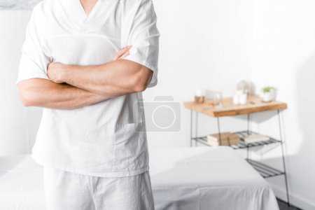 Photo for Cropped view of masseur standing with crossed arms and looking at camera in clinic - Royalty Free Image