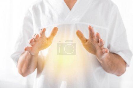 Photo pour Vue recadrée du guérisseur nettoyer aura sur blanc - image libre de droit