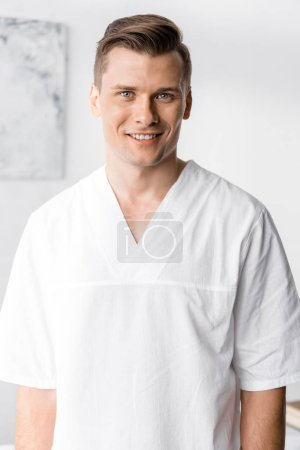 Photo for Front view of smiling masseur looking at camera in clinic - Royalty Free Image
