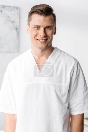 Photo pour Vue de face du masseur souriant regardant la caméra à la clinique - image libre de droit