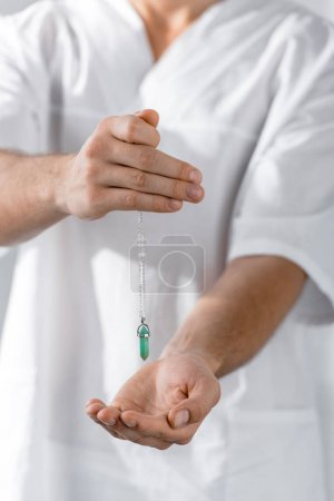 Photo for Cropped view of hypnotist holding green stone in clinic - Royalty Free Image