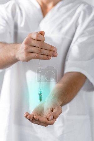 Foto de Vista recortada de hipnotizador sosteniendo piedra verde en la clínica - Imagen libre de derechos
