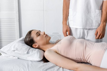 Photo for Cropped view of masseur standing near woman lying on massage table with closed eyes - Royalty Free Image