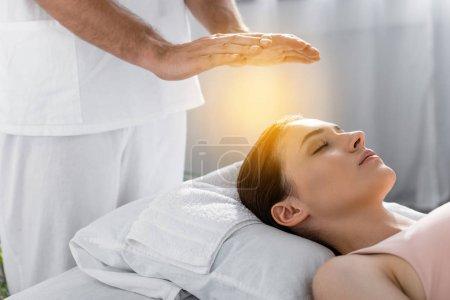 Photo pour Vue raccourcie du guérisseur restant près du patient sur la table de massage et l'aura de nettoyage - image libre de droit