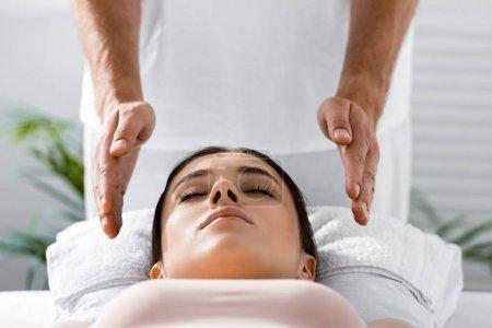 Photo pour Vue recadrée du guérisseur debout près du patient sur la table de massage et l'aura de nettoyage - image libre de droit