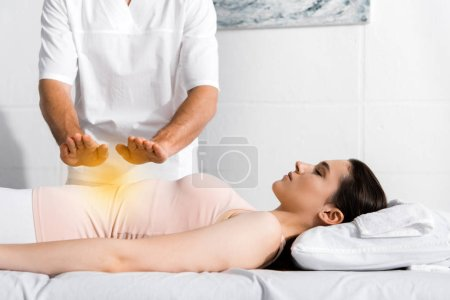 Photo for Cropped view of healer standing near woman and holding hands above her stomach - Royalty Free Image