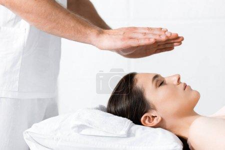 Photo pour Vue recadrée du guérisseur debout près de la femme et tenant les mains au-dessus de sa tête - image libre de droit