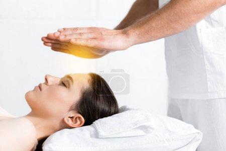 Foto de Vista recortada del sanador de pie cerca de la mujer y torse las manos por encima de su cabeza - Imagen libre de derechos