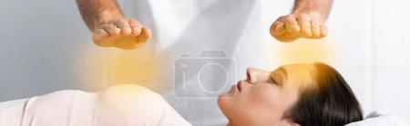 Photo pour Tir panoramique de guérisseur debout près de la femme avec les yeux fermés et se tenant les mains au-dessus de son corps - image libre de droit
