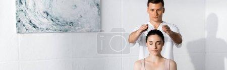 Photo pour Plan panoramique de jeune femme assise les yeux fermés tandis que guérisseuse nettoie son aura - image libre de droit