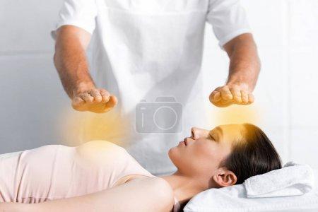 Photo pour Vue recadrée du guérisseur debout près de la femme les yeux fermés et tenant les mains au-dessus de son corps - image libre de droit